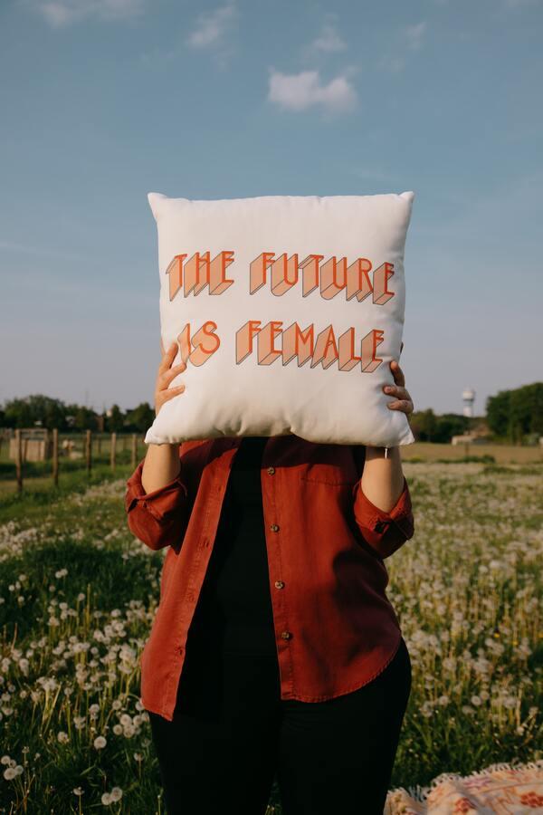 """foto de uma mulher em um campo aberto segurando uma almofada tampando o rosto com a escrita """"The future is female"""""""