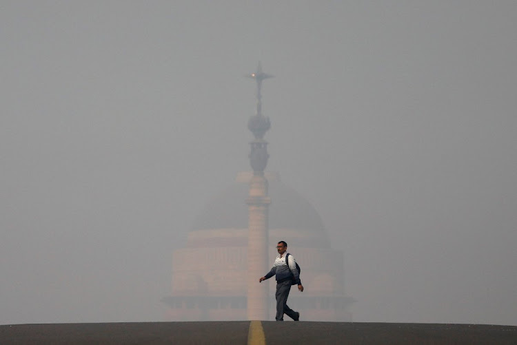 A man walks in front of India's presidential palace on a smoggy morning in New Delhi.