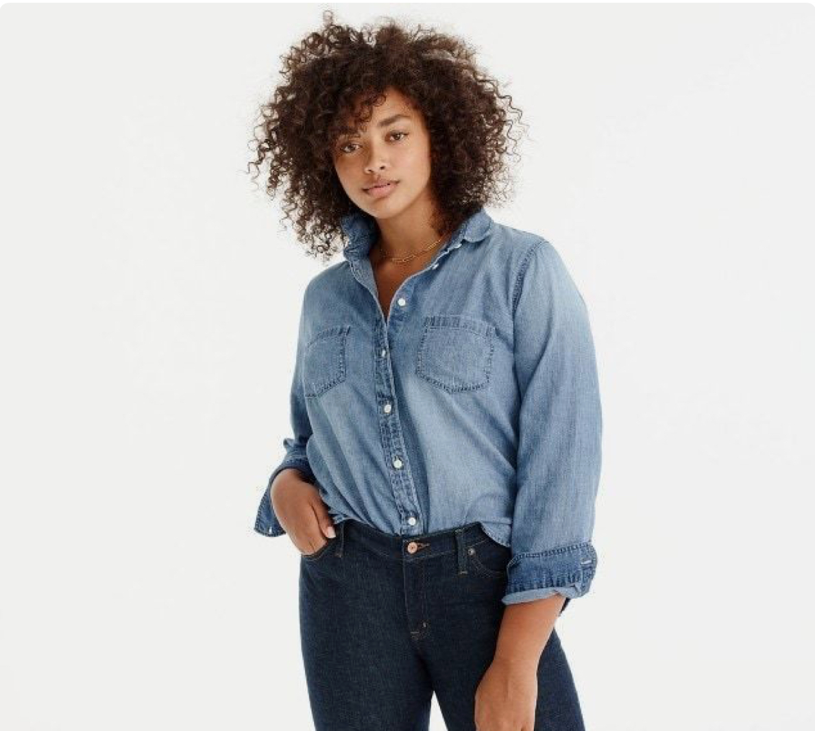 A woman is wearing a large hat blue chambray button up tucked into a dark pair of jeans