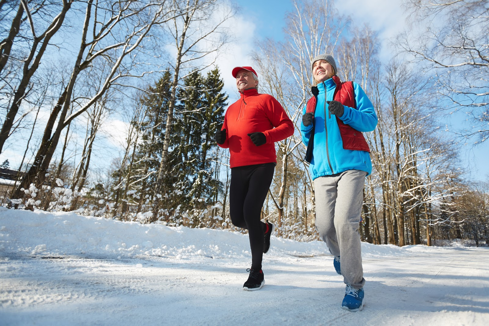 Man and woman jogging in the snow to shake off the winter blues
