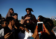 Afghans take a picture with a Taliban militant in Kabul, Afghanistan, on June 16 2018. US President Donald Trump and the Taliban pledged to take the fight to each other following the precipitous collapse in talks.
