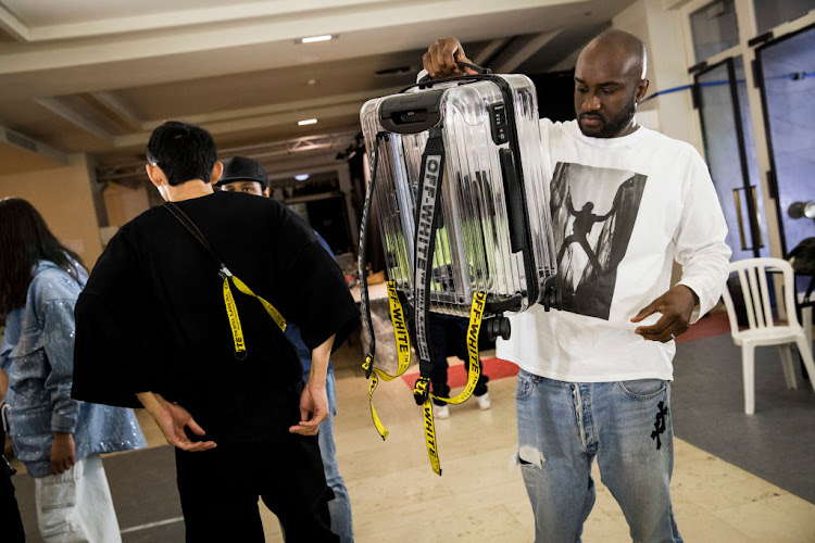 Designer Virgil Abloh poses backstage with a Off-white x Rimowa suitcase prior to the Off-White show at Paris Fashion Week 2018.