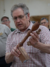Photo: Bill Autry shows off some spindle work -- the candle stick, inspired by the work of Barbara Dill, has been turned in four axes, with twists on the cup and shaft done in opposite directions.  He holds parts for another one.  Bill will be our demonstrator in December.
