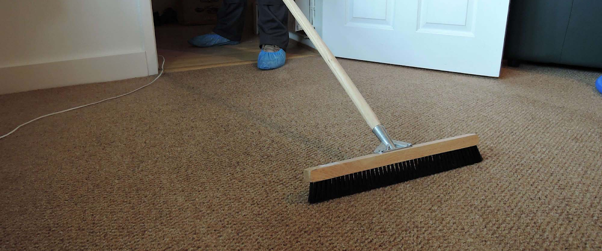 A carpet being dusted with a broom in Reading