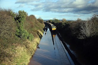 Photo: TAUNTON, ENGLAND - NOVEMBER 21:  A train waits to pass along flooded track close to the village of North Curry on November 21, 2012 near Taunton, England. Heavy rain overnight has brought widespread disruption to many parts of the UK particularly in the Somerset and Wiltshire and weather forecasters have warned of more wet and windy weather to come.  (Photo by Matt Cardy/Getty Images)