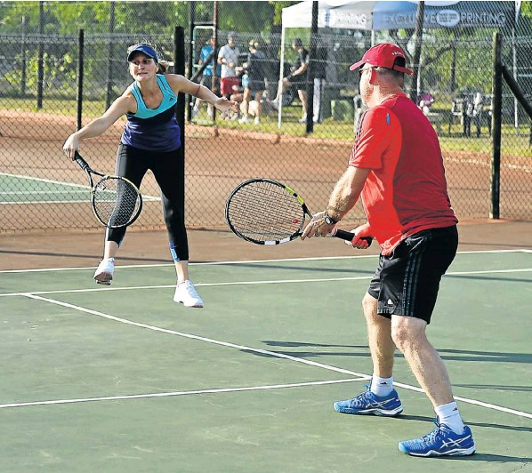 Watched by partner Theo Smit, Elaine van Zyl returns a backhand during a match in the Walmer Lawn Tennis Club Mixed Doubles Challenge on Saturday. Smith and Van Zyl won the A section