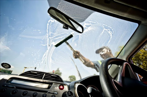 Window washers wash a motorist's windscreen at a traffic light in Pretoria on March 14, 2012. Picture GALLO IMAGES