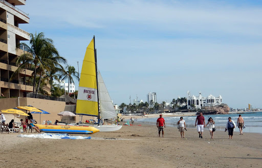 mazatlan-beachfront.jpg - A sailboat and banana boat rest on the beach of Mazatlan, Mexico.