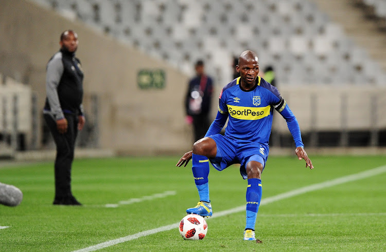 Cape Town City captain and defender Thamsanqa Mkhize in action during the Absa Premiership match against Lamontville Golden Arrows at Cape Town Stadium in Cape Town on August 18 2018 as head coach Benni McCarthy watches on in the background.