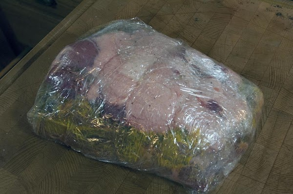 Wrap the pork shoulder in two layers of cling film.