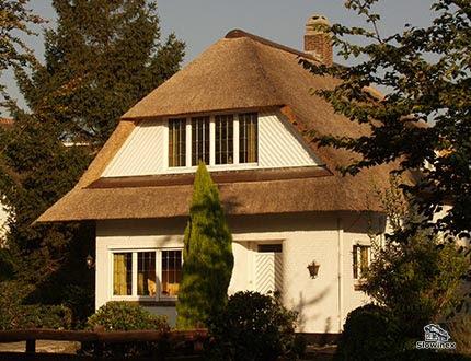 Dwupiętrowy biały dom ze spadzistym dachem krytym trzciną