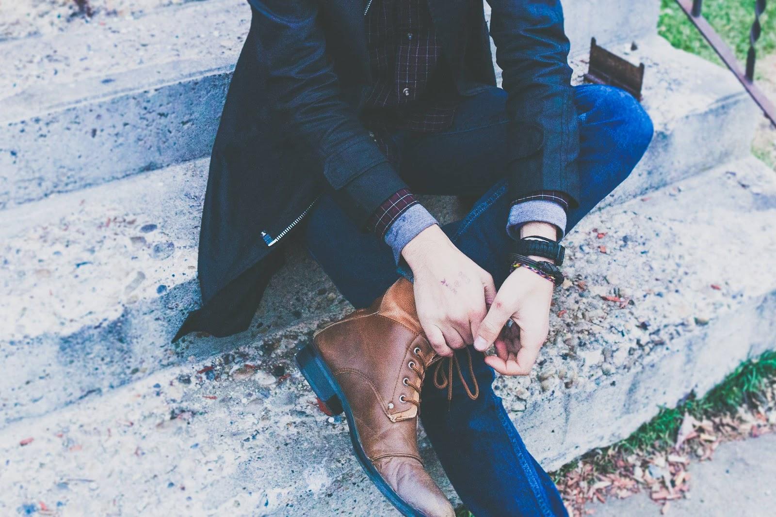 uomo-seduto-scarpe-eleganti-jeans