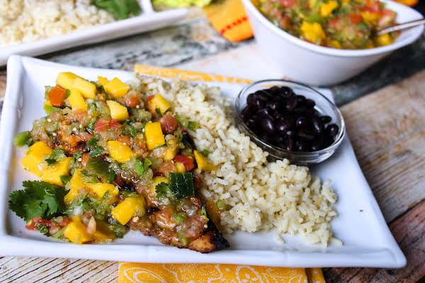 Grilled Jerk Chicken With Mango Salsa On A Plate With Rice And Beans.