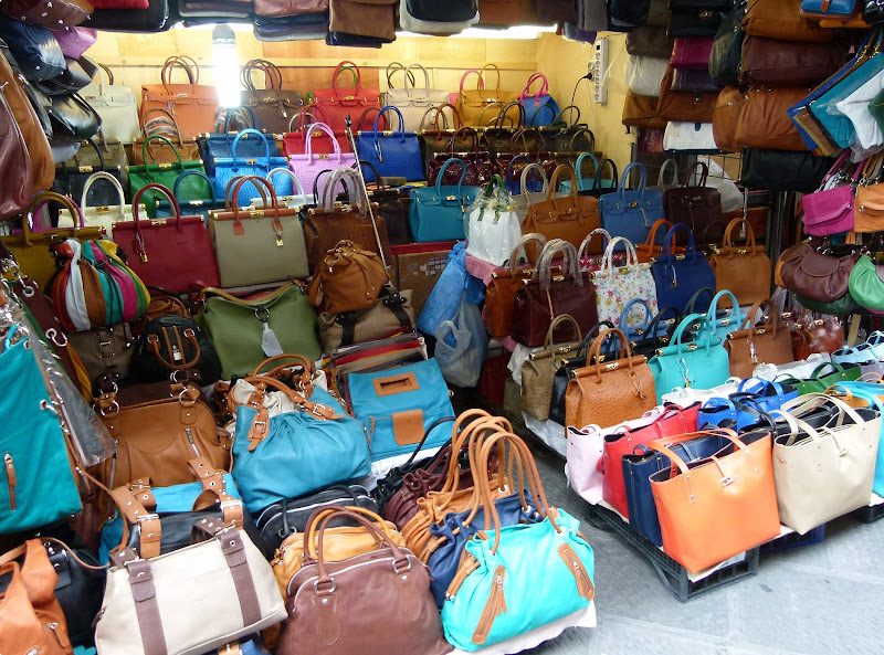 Handbags and leather goods for sale at San Lorenzo Market in Florence.