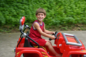 Little boy driving red ride-on Jeep