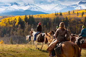 "Photo: Everyone looks good on a horse! This was a remarkable Thanksgiving day. The sky was dark and dramatic in the background, but the sun managed to peak out for a few moments. What was remarkable for me is that I managed to take this photo while riding a horse!  Perhaps it would be easier to take a shot with a small point and shoot, or with a wide angle lens, but instead I used my 70-200 telephoto to increase the size of the mountains in the background.I positioned the riders on the right side of the frame, facing into the view to satisfy that unconscious urge to ""see what the riders are looking into"".  The somewhat ridiculous setting on this photo is the fact that I have a high shutter speed of 1/2500 of a second. At first this might look like a mistake, but in reality, holding a telephoto lens or a moving horse will create a lot of motion blur, and this high shutter speed will prevent that blur from happening."