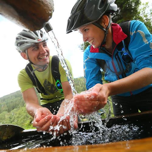 Zwei Radfahrer erfrischen sich an einem Brunnen mit Wasser